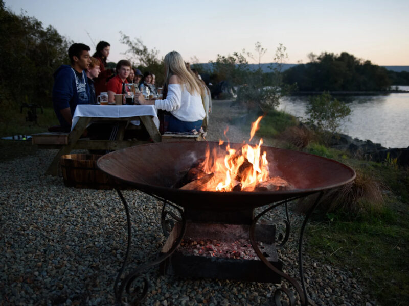 People eating by the lake on a picnic table with a firepit
